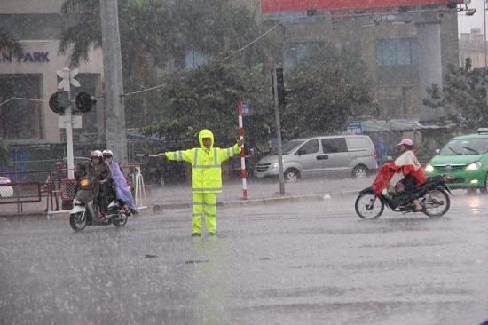 Ngay từ sáng sớm, lực lượng CSGT đã vất vả phân làn trong mưa.